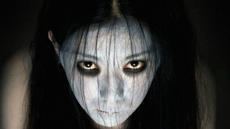 A young woman in white face paint grudge